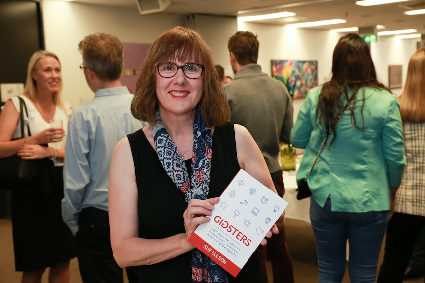 Sue Ellson holding up a copy of her book Gigsters at its launch in 2019