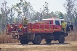 An NT Fire and Rescue fire truck is parked next to bushy scrub with two firefighters.
