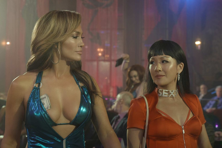 Jennifer Lopez on left and Constance Wu on right, wearing tight tops and looking at each other and smiling, club in background.