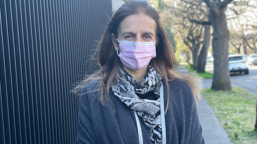 A woman in a pink surgical mask standing on a footpath