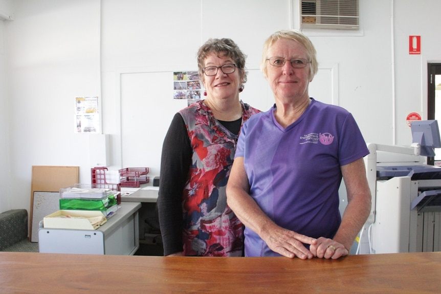 Two women standing behind a desk in an office.