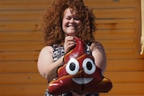 A woman with curly hair smiles as she holds a balloon with a funny face.