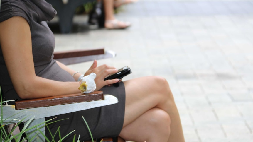 A woman sits on a bench using a mobile phone.