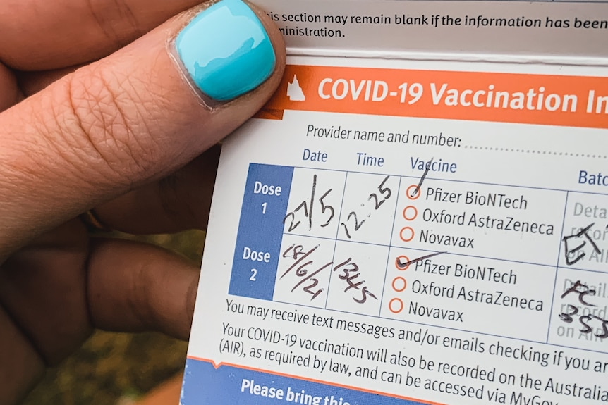 a close up image of a completed vaccination card in hand