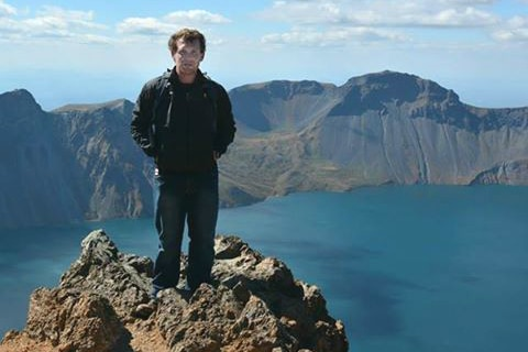 man standing on a cliff above a lake