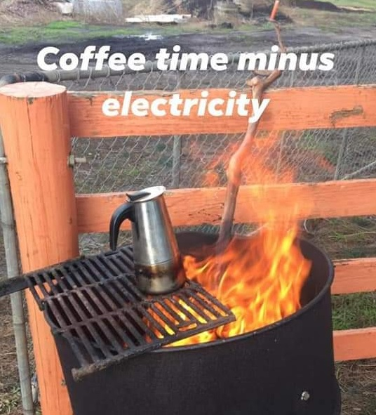 A coffee pot sits on top of a grill plate over a fire
