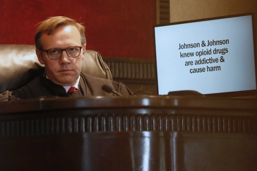 A judge listens during opening arguments for the trial with a screen next to him.
