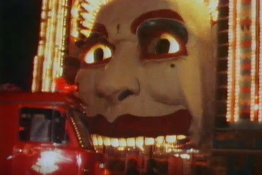 a fire engine in front of a big clown face