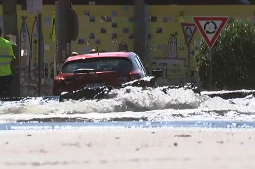 Water gushes along the road.
