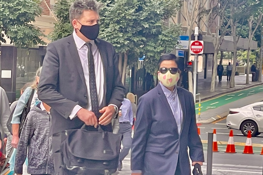 Lawyer Nick Dore, left, and My Ut Trinh, right, entering Brisbane court before needles in strawberries charges dropped