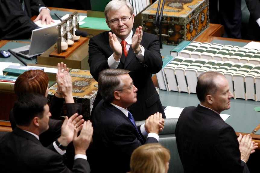 Kevin Rudd, in a dark suit stands with his back to the dispatch box and his hands raised to people unseen in lower house gallery