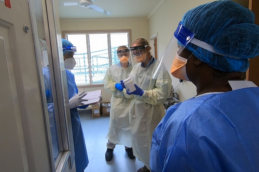Four hospital staff wearing masks and gowns stand in a hospital room.