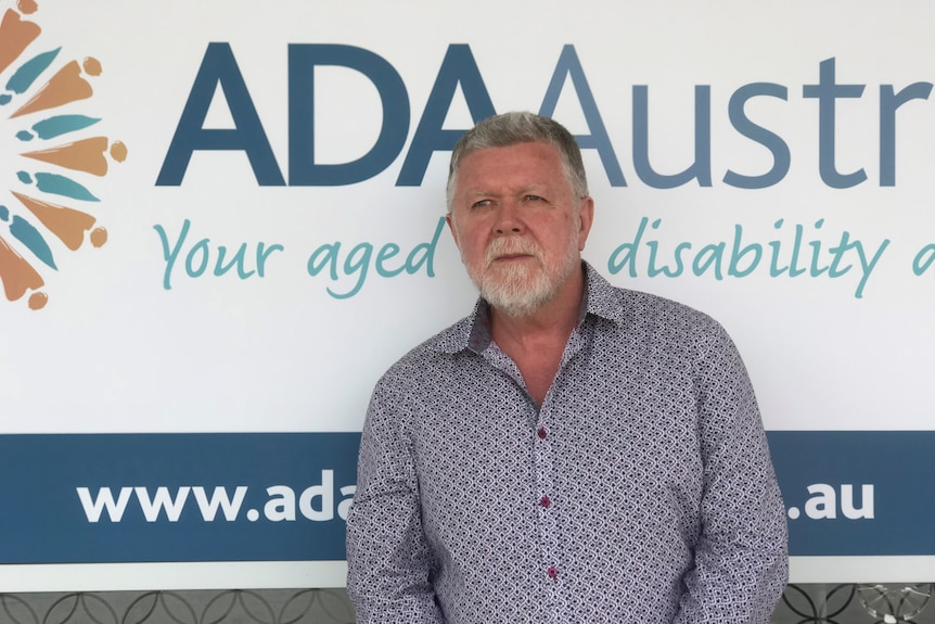 A man with a beard and grey hair standing front of an ADA Australia sign.