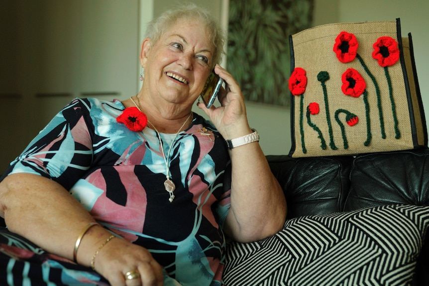Older woman sits on a couch in a comfortable position, holding a mobile phone to her ear and smiling in a happy conversation.
