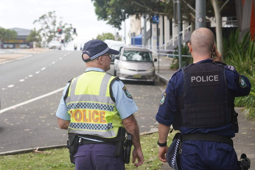 Two police officers, viewed from the back, walking along a street in Wollongong