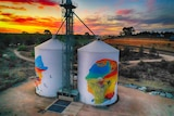 Two silos with colourful paintings are backdropped by a beautiful swirling sunset of red, orange, yellow, blue, pink and purple.