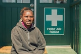 Nerissa Narburup sitting in front of a health service's first aid room.
