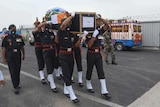 Indian army soldiers dressed in military uniform carry the coffin of their colleague.