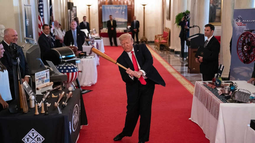A man with blond hair wearing a suit with a red tie swings a bat in a room while men stand around him.