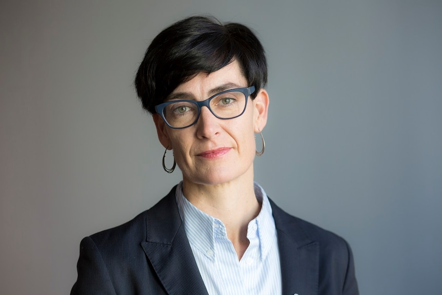 A head shot of Commissioner Liana Buchanan who has short black hair and wears glasses.