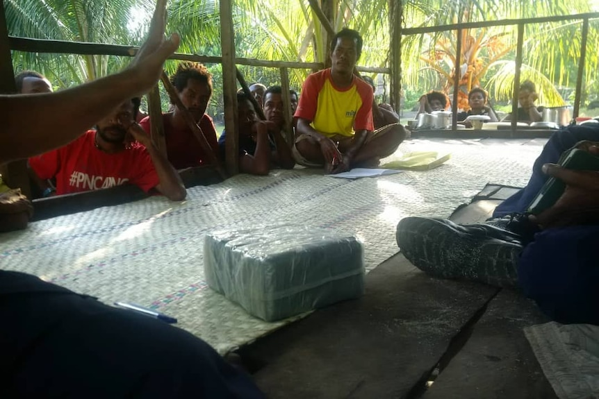 People sitting around a parcel containing what is believed to be drugs.