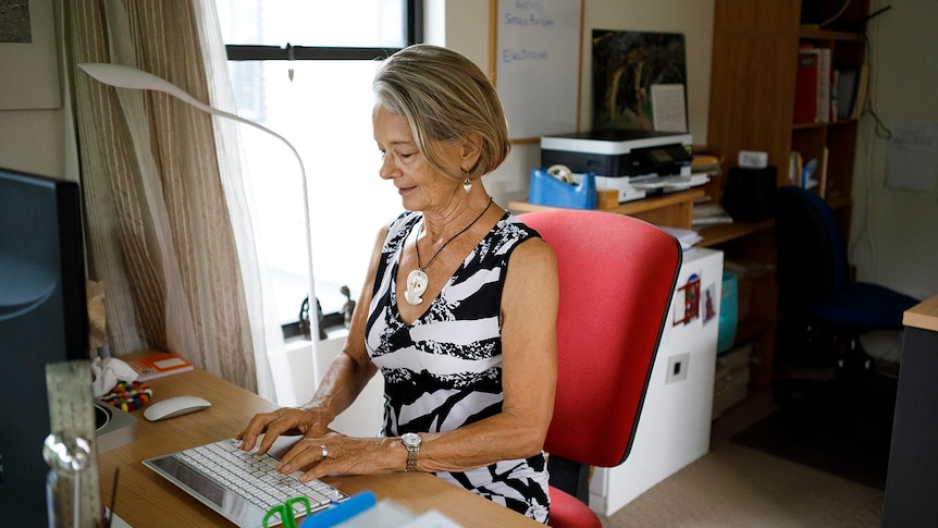 A woman sits at a desk typing on a keyboard for a story on share housing when you're retired.