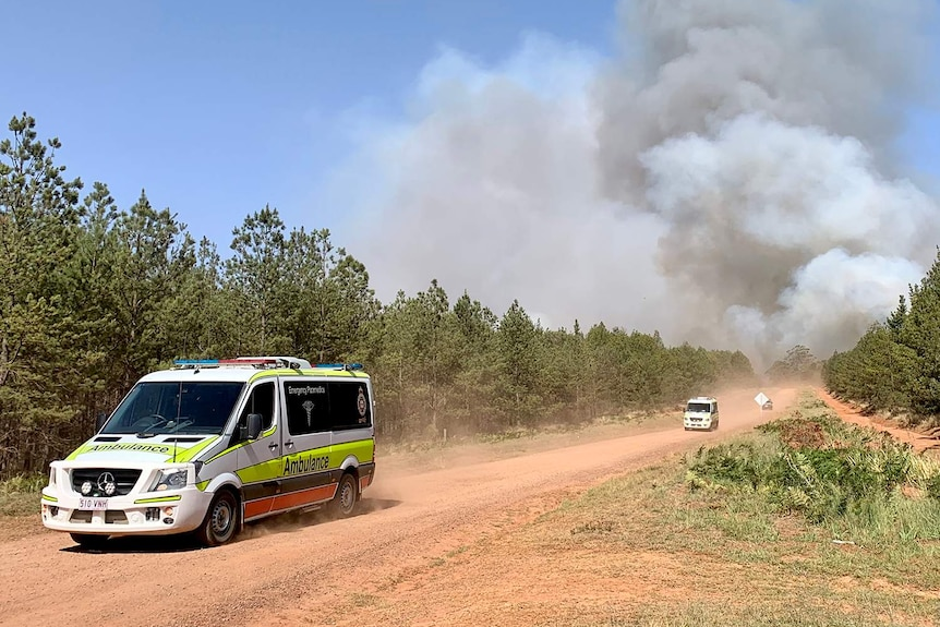 A procession of ambulances heading from Pechey bushfire with a smoke cloud behind them.