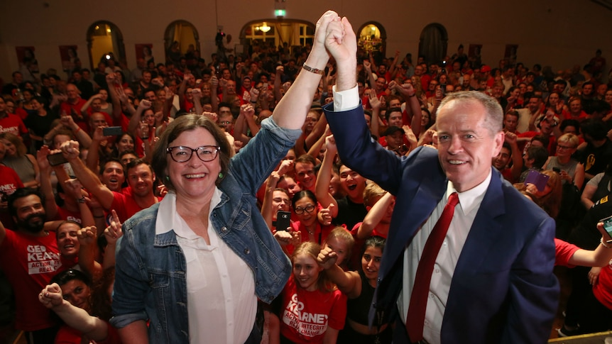 Bill Shorten and Ged Kearney join hands with a crowd of supporters behind them.
