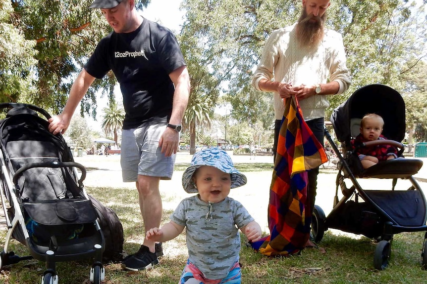 Two fathers stand in a park one toddler stands and another baby sits in a pram for a dads' support group.