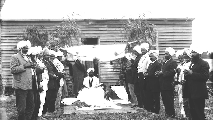 Siva Singh stands under an awning, surrounded by Sikh men.