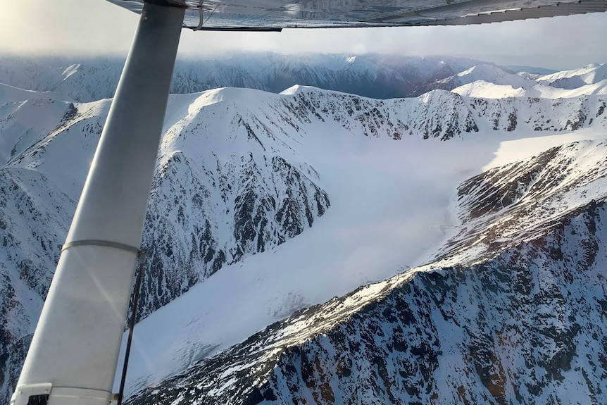 Aerial shot of snow-capped mountain range.