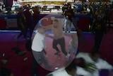 CCTV still of massive brawl at a strip club. One man is spotlighted.