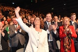 Julia Gillard holds up a hand and waves as she is cheered at the Labor election launch.