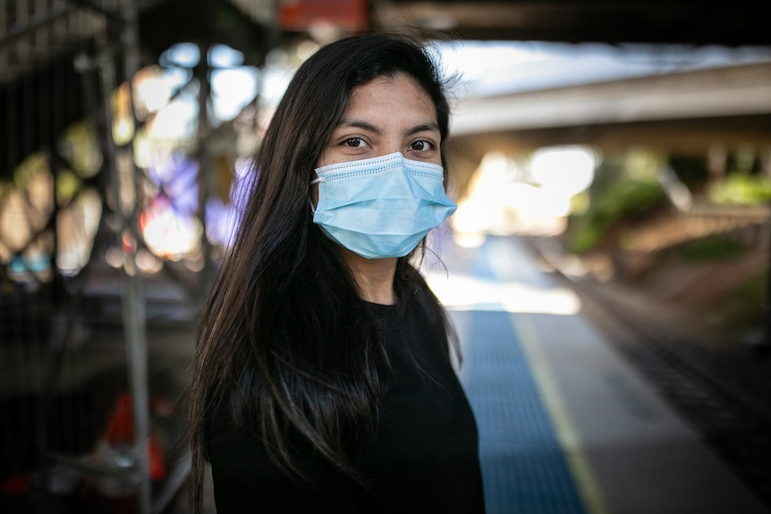 a young woman wearing a mask looking
