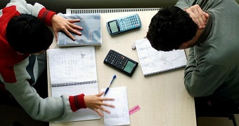 Two people complete homework at a desk.