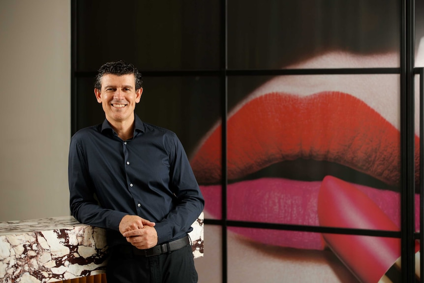 A man stands in front of an add featuring lipstick being applied to lips.