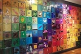 A wall full of colourful record covers, green, blue, pink and yellow.