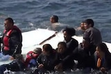Migrants on top of a sinking boat off Greece's coast