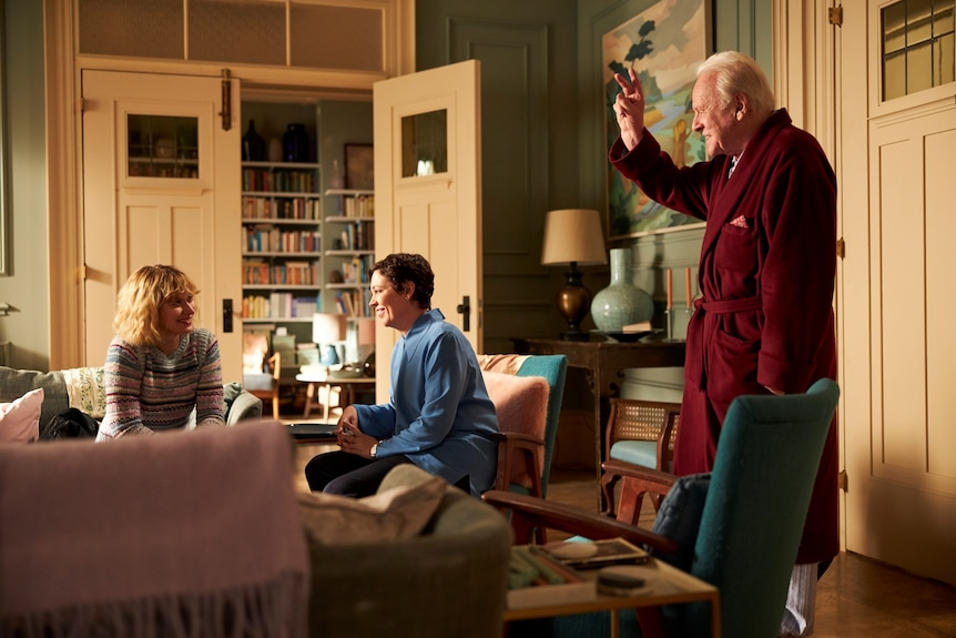 Imogen Poots, Olivia Colman and Anthony Hopkins all talking in a lounge in the film The Father