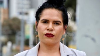 A close up shot of a woman with black hair, a mauve jacket and red lipstick.
