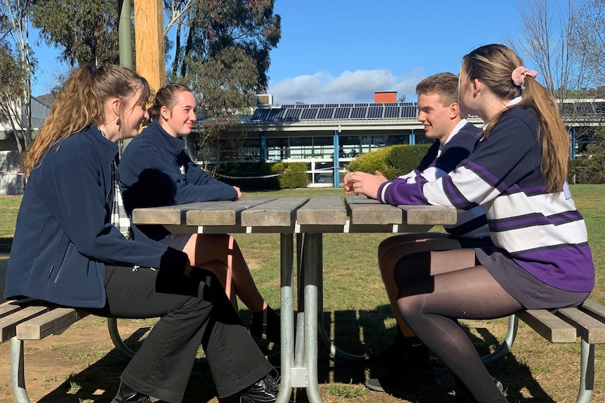 Four teenagers sitting at on school bench