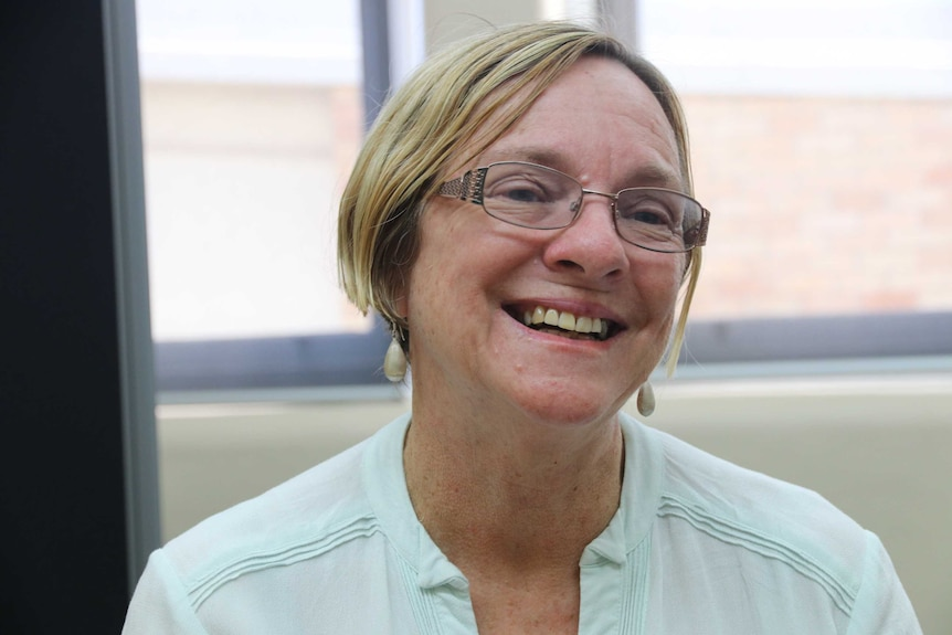 A woman in glasses smiles