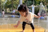 A toddler playing with water at an outdoor fountain.