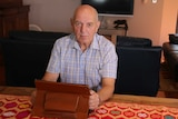 John Allen sitting at a table in front of a television. He is holding a tablet computer in a leather type case.