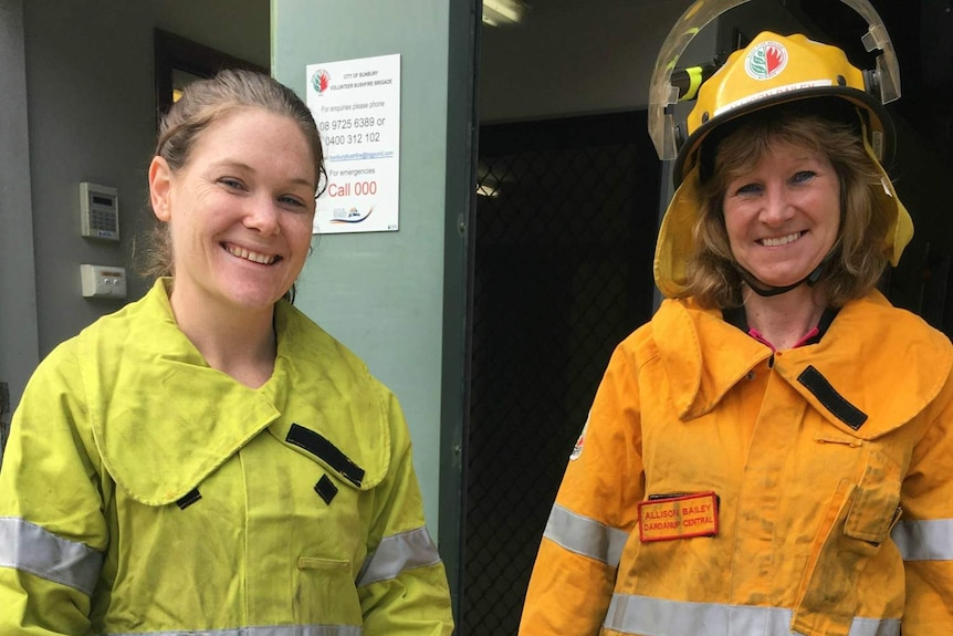 Two women in firefighting uniforms and helmets.