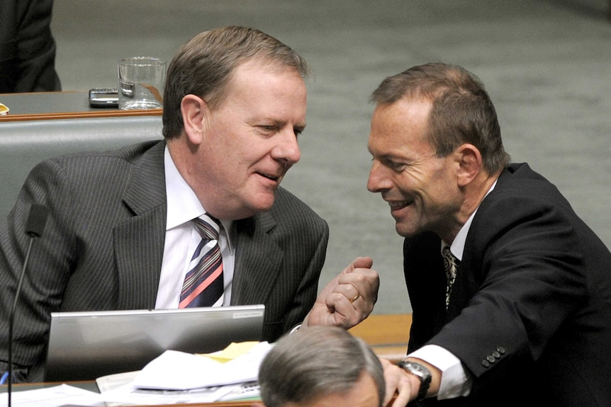 Tony Abbott smiles as he leans in to speak to Peter Costello
