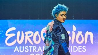 Montaigne looks back at the camera, displaying the back of her blue jacket.