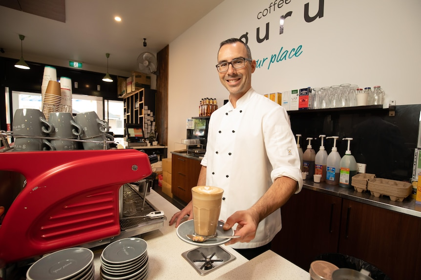 A man serves coffee from behind a machine in a cafe.