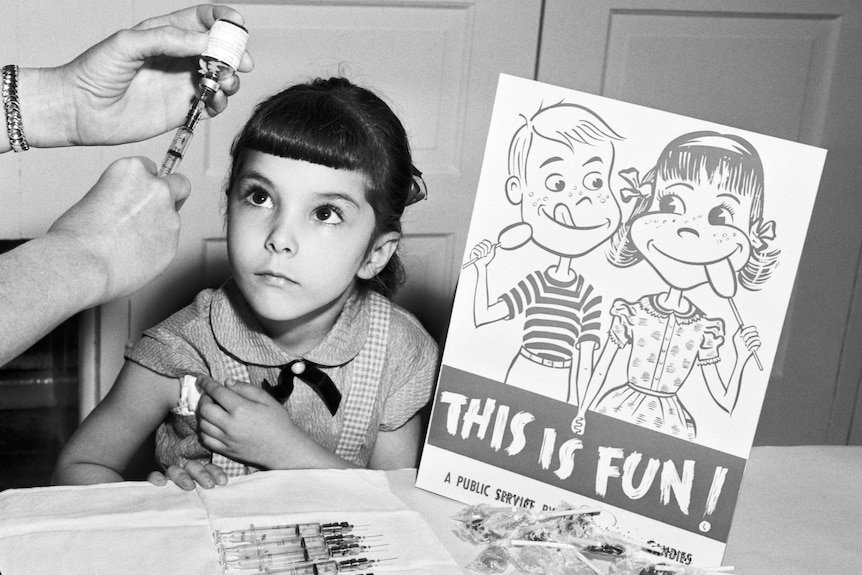 A little girl looks at a needle as she prepares to get the polio vaccine next to a school sign in the 1950s.