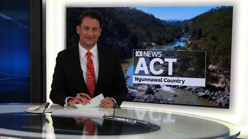 Bourchier at news desk with plasma screen showing ACT ABC News with Ngunnawal Country written underneath.